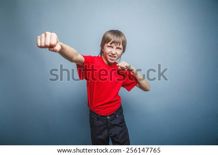 Boy, teenager, twelve his years  red  in shirt, red showing  fists  - stock photo