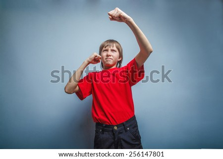 Boy, teenager, twelve years in  red shirt, showing his fists - stock photo
