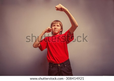 Boy, teenager, twelve years in  red shirt,  showing his fists retro - stock photo