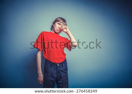 Boy, teenager, twelve years in  red T-shirt, hand wipes tears, sadness instagram effect style - stock photo