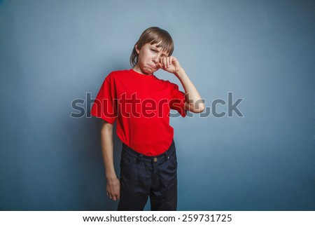 Boy, teenager, twelve years in the red T-shirt, hand wipes tears, sadness - stock photo