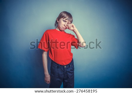 Boy, teenager, twelve years in the red T-shirt, hand wipes tears, sadness instagram effect style - stock photo