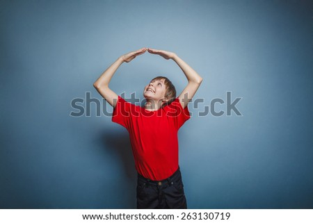 Boy, teenager, twelve years in the  red t-shirt, made from the hands of a house over his head - stock photo