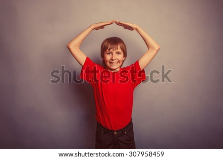 Boy, teenager, twelve years in the red t-shirt, made his hands above his head house retro - stock photo