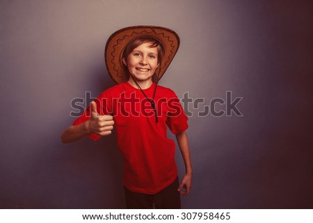 Boy, teenager, twelve years in the red t-shirt with a cowboy hat showing sign yes retro - stock photo