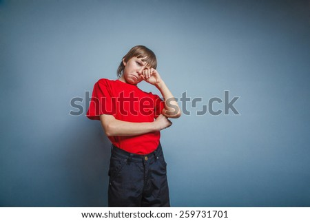 Boy, teenager, twelve years red in T-shirt, hand wipes tears, sadness - stock photo