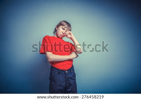 Boy, teenager, twelve years red in T-shirt, hand wipes tears, sadness instagram effect style - stock photo