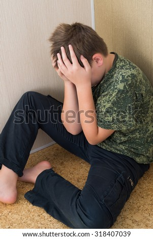 Boy teenager with depression sitting in the corner of the room