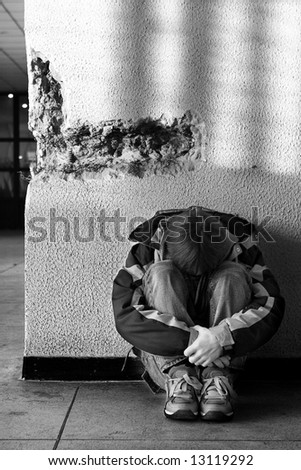Boy teens sitting on the floor alone in city (series teenagers) - stock photo