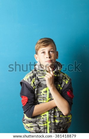 boy thinking and looking up, blue background - stock photo