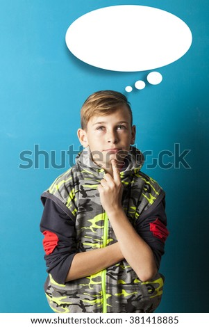boy thinking and looking up, blue baclkground - stock photo