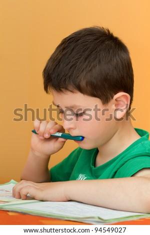 boy thinking on homework from school in workbook - stock photo
