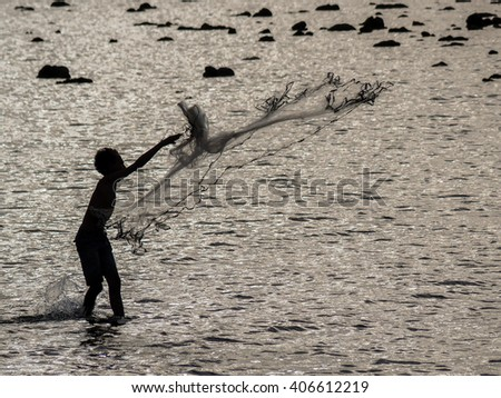 Boy throwing fishing net after dusk - stock photo