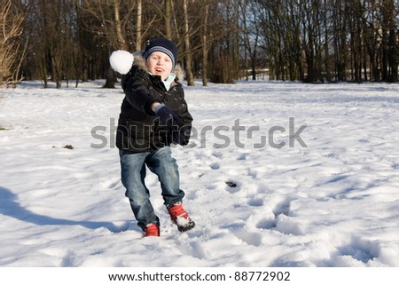 Boy throwing snowball in cold winter day