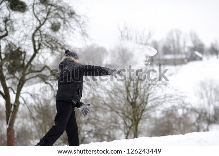 Boy throwing snowballs - stock photo