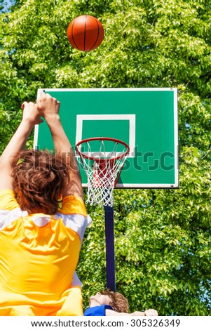Boy throwing up the ball during basketball game - stock photo