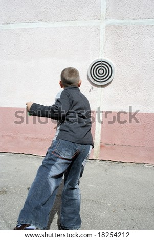 Boy throws dart in a target - stock photo