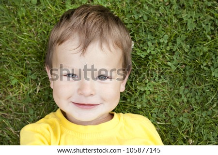 boy toddler is relaxing in the grass during summer days - stock photo