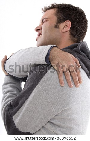 boy touching the back with a pained expression on his face - stock photo