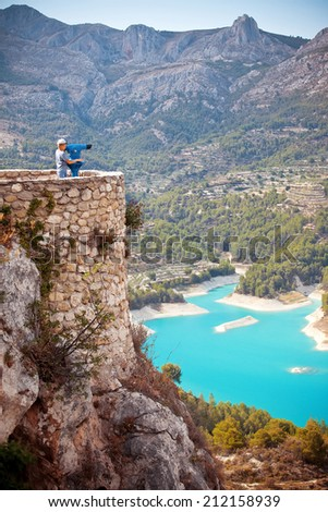 Boy tourist looking in telescope on the observation deck to neautiful lake in Guadalest, Spain