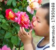 Boy try hold and smell flower - stock photo