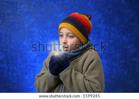 Boy trying to warm his hands in winter outfit.
