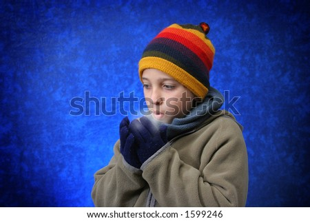 Boy trying to warm his hands with his breath in winter outfit.