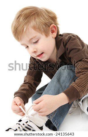 Boy tying his shoes - stock photo