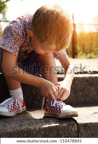 Boy tying the laces on sneakers sitting on the steps - stock photo