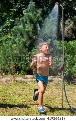 Boy under a shower in the garden in hot day - stock photo