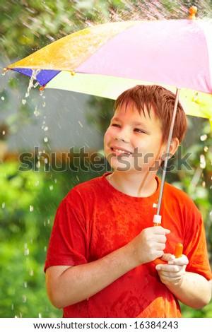 boy under an umbrella during a rain ... - stock photo