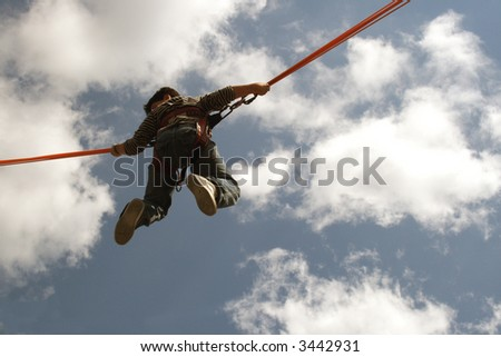 Boy up in the air while bungee jumping on a trampoline