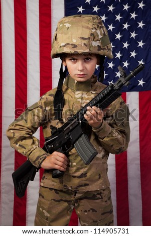 Boy USA soldier in front of American flag with rifle. Young boy dressed like a soldier - stock photo