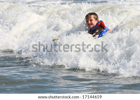 Boy using a body board in the middle of a wave - stock photo