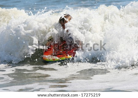 Boy using a body board with a wave crashing over him - stock photo