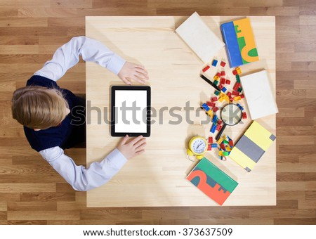 Boy using a digital tablet, view from above