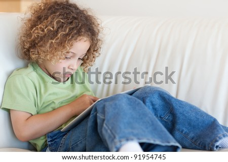 Boy using a tablet computer in a living room - stock photo