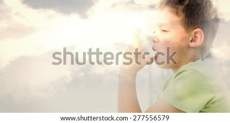 Boy using an asthma inhaler in clinic against grey cloudy sky - stock photo
