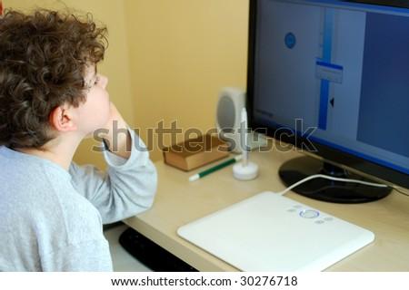Boy using computer at home - stock photo