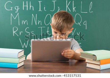 Boy Using Digital Tablet With Stack Of Books On Desk In Classroom