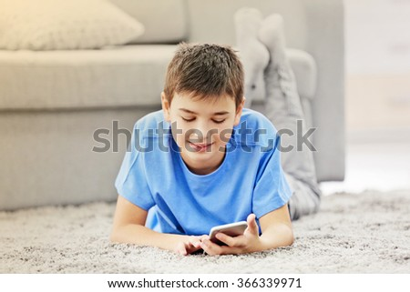 Boy using his mobile phone at home - stock photo