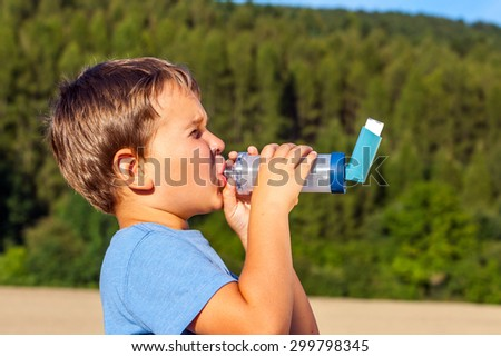 Boy using inhaler for asthma in village with summer sunset and forest