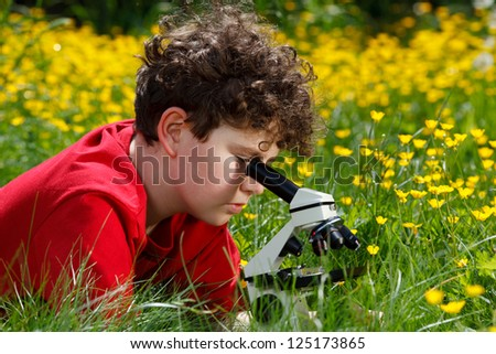Boy using microscope outdoor