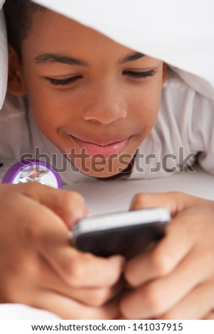 Boy Using Mobile Phone Under Duvet - stock photo