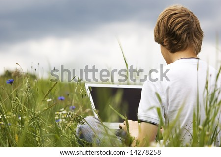 Boy using notebook outdoor on the field - stock photo