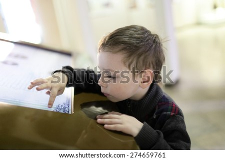 Boy using touch screen in the museum - stock photo