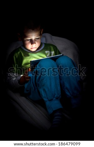 Boy very carefully looking at the tablet - stock photo