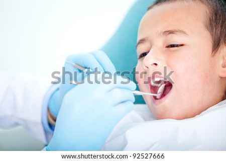 Boy visiting the dentist for cleaning and checkup - stock photo