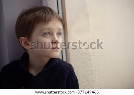 Boy waiting by window for stop raining. Loneliness and waiting concept. Rainy day - stock photo