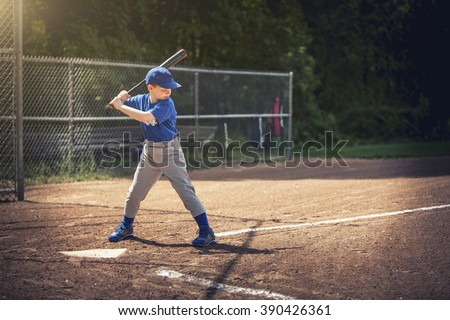 Boy waiting for the ball in a baseball game - stock photo